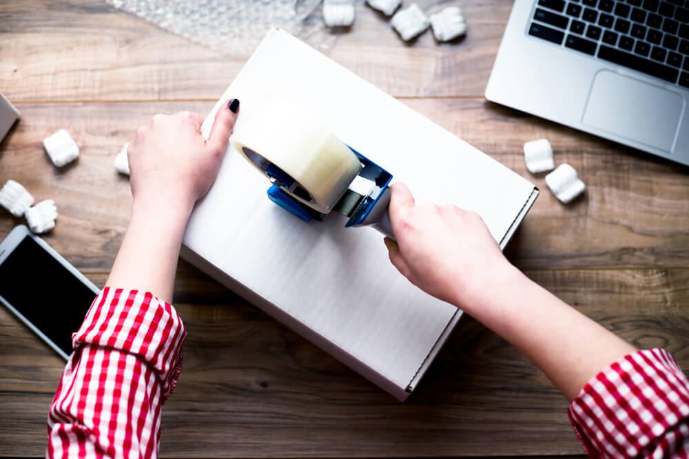 Jonge vrouw verpakt doos met tape fulfilment